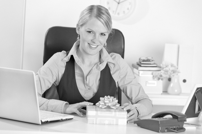 Happy business woman with present box at office desk