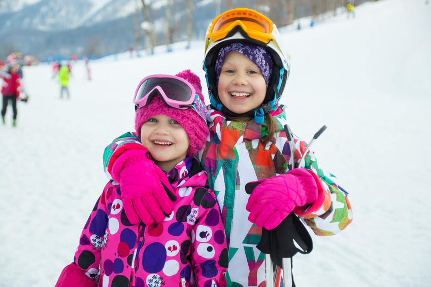Portrait of two little girl in  ski helmet and mask in winter resort