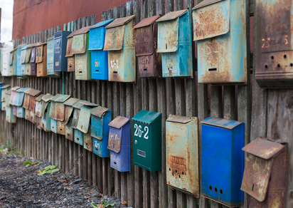 Set of old mailboxes with rust attached to the fence