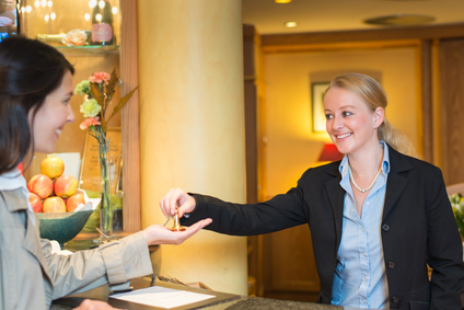 Smiling friendly hotel receptionist standing behind the service desk in a hotel lobby booking in a female client handing her the room keys for her stay during her vacation