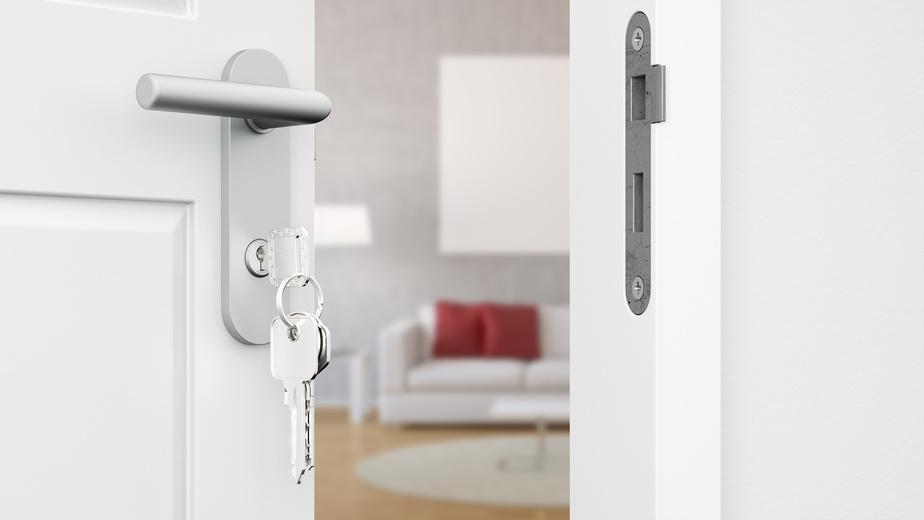 Geöffnete Tür mit Schlüssel vor einem Wohnzimmer