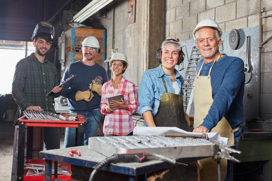 Gruppe Arbeiter und Lehrlinge als erfolgreiches Team in einem Industrie Betrieb