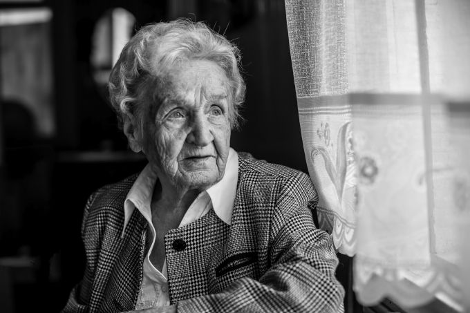 Portrait of stern old women, black and white near the window.